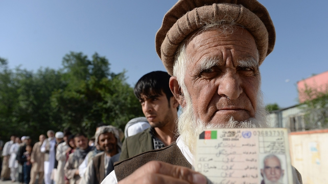 An Afghan resident wanting to vote poses for a photograph with his identity card as he waits for voting to start