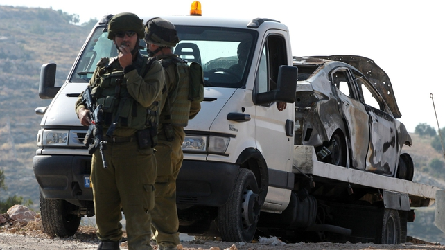 Israeli soldiers secure the area around a burnt car reportedly connected to the disappearance of three Israeli teen settlers