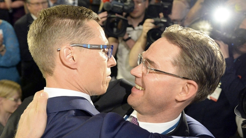 Alexander Stubb (L), new chairman of Finland's National Coalition party, is hugged by his predecessor Jyrki Katainen (R) after his election in the party's congress