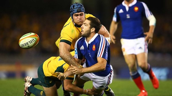Remi Tales of France offloads under pressure from two Australian tacklers