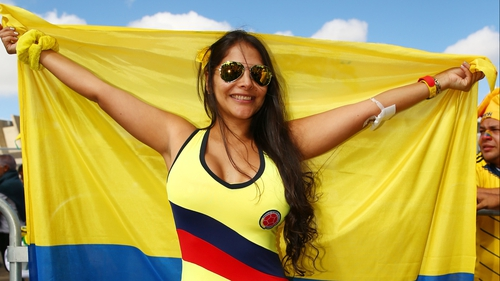 A Colombia fan holds the flag proudly at the start of World Cup Day 3