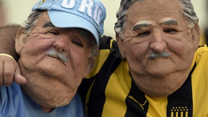 Fans wear masks of Uruguayan President Jose Mujica as they cheer prior to Uruguay vs Costa Rica