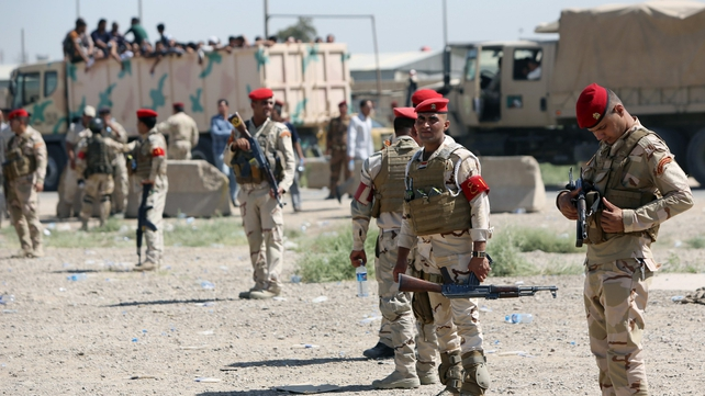 Iraqi soldiers stand in front of volunteers to fight along side the Iraqi security forces