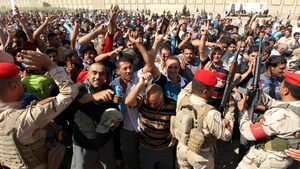 Iraqi men, who volunteered to fight against Jihadist militants, gather around buses in Baghdad ahead of military training