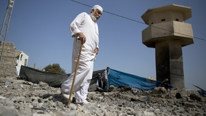 A Palestinian man walks on the rubble past a crater following an air strike by the Israeli airforce on Gaza