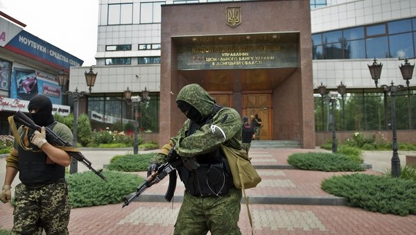 Pro-Russian forces stand guard outside a branch of the National Bank of Ukraine in Donetsk