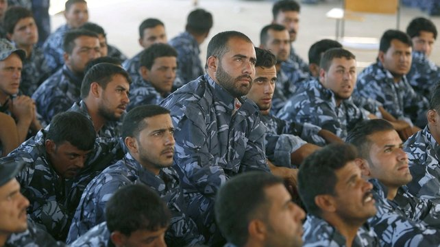 Iraqi volunteers in their new uniforms gather at a centre following a speech by the Iraqi prime minister