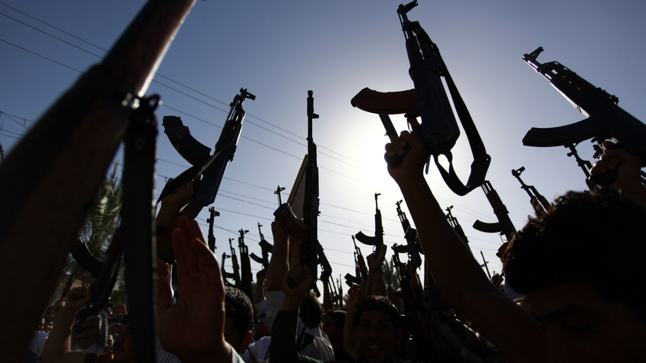 Iraqi Shiite tribesmen brandish their weapons as they gather in the southern Shiite Muslim shrine city of Najaf