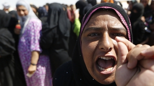 A displaced Iraqi woman shouts as she queues with others to register at a temporary refugee camp set up in Aski Kalak