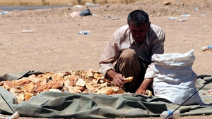 A refugee carries food at a camp near the city of Erbil, northern Iraq