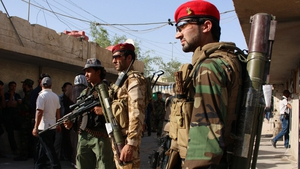 Iraqi soldiers stand guard as tribesmen gather in the southern city of Basra