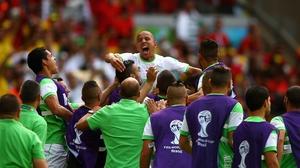 The Algeria squad lift Feghouli in celebration