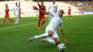 Algeria defender Madjid Bougherra reaches for the ball, as Belgium begins to apply steady pressure in the second half of play
