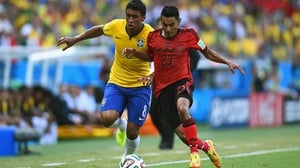 Brazil midfielder Paulinho and Mexico midfielder Jose Juan Vazquez compete side by side for the ball, during a scoreless opening half which saw great defensive efforts on both sides of the ball
