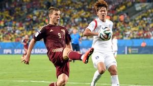 Russia forward Alexander Kokorin extends his reach against Korean defender Kim Young-Gwon