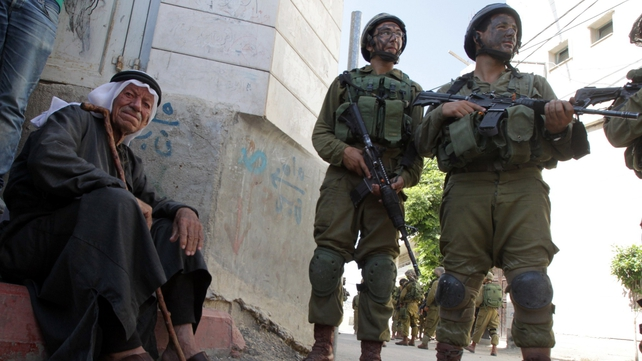 An elderly Palestinian man sits near Israeli soldiers taking part in a search operation for three Israeli teenagers