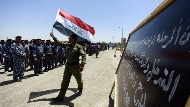 A member of Iraq's security forces wave his national flag as newly recruited men gather