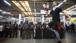 A juggler on a unicycle performs in front of police during an anti-World Cup protest at the Carrao Metro Station