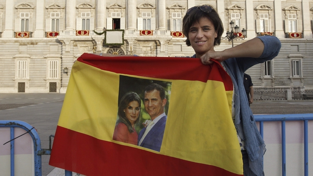 A woman holds a flag bearing the portraits of King Felipe VI and Queen Letizia in front of the Royal Palace in Madrid