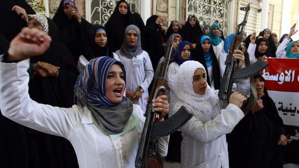 Iraqi Shia women hold their weapons as they gather to show their willingness to join Iraqi security forces
