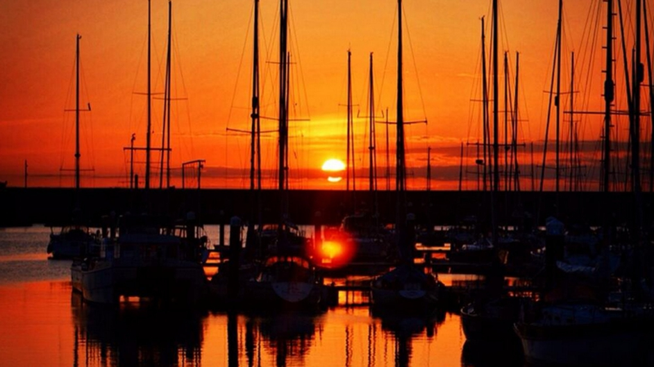 The sun descends behind boats docked at Dún Laoghaire harbour (Pic: @Migr6)