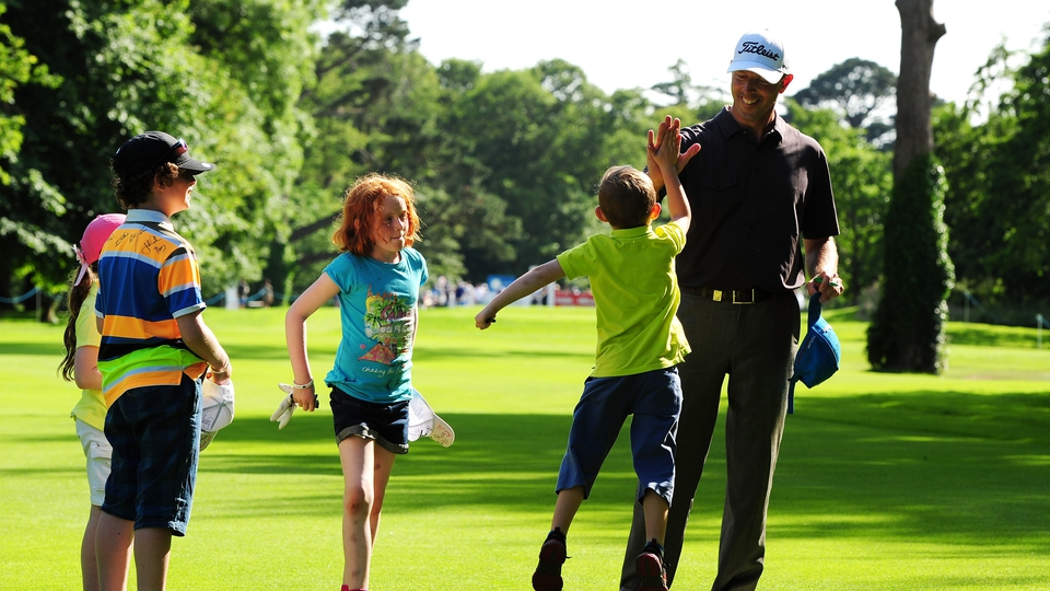 Soren Hansen of Denmark gets a high five from a young autograph hunter on 18th fairway during the Pro-Am day
