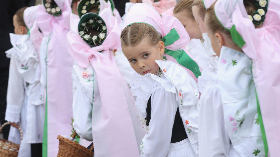 Sorbian minority girls in traditional folk dress walk in a procession following an outdoor mass during Corpus Christi in Crostwitz, Germany