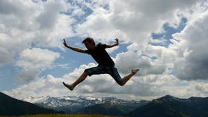 A young boy jumps on a trampoline near the 'Bichl Alm' in the Grossarl Valley in the Alps, Austria