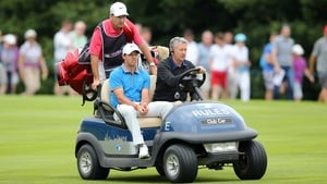Rory McIlroy and caddie JP Fitzgerald are driven back to the fourth tee box to retake his drive on day two