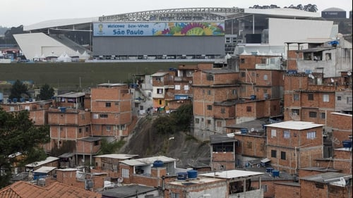 The Arena de Sao Paulo stadium dominates the skyline above the poor neighbourhood of Itaquera