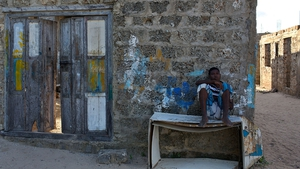A young boy sits outside a boat workshop in the resort town of Lamu on Lamu Island, part of the Lamu Archipelago in Kenya