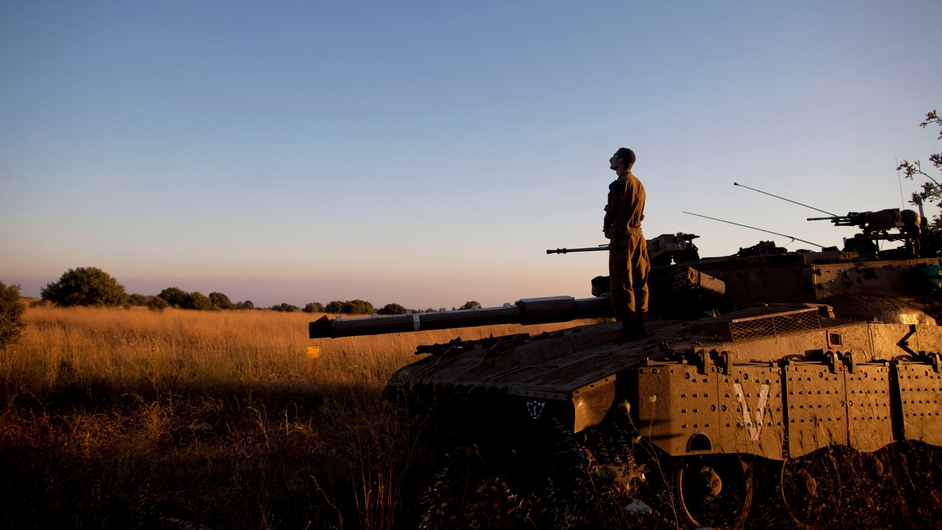 An Israeli soldier prays on a Merkava tank on the Israeli-Syrian border near Quneitra