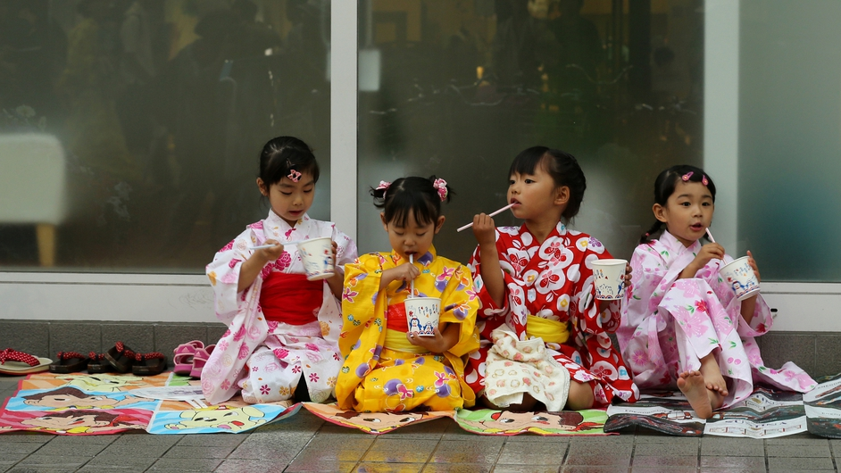 Girls dressed in 'Yukata' summer kimonos eat dessert during the annual Himeji Yukata Festival in Japan