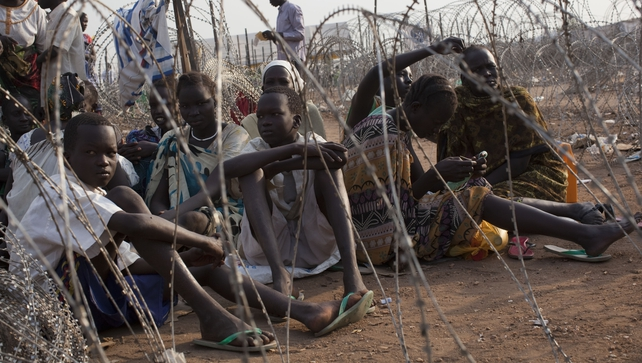 Displaced people wait for food in a camp in Juba