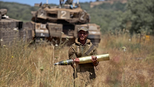 An Israeli soldier carrying a shell at a field next to tanks deployed on the Israeli-Syrian border