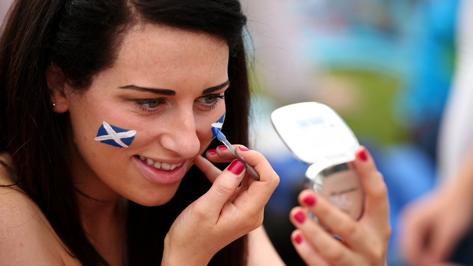 An Andy Murray fans paints her face in the Scottish colours before day one of the Wimbledon Lawn Tennis Championships