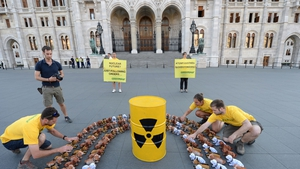 Greenpeace activists prepare 110 bobblehead dogs in front of the parliament building in Budapest during a protest against planned upgrades to the country's nuclear power plant