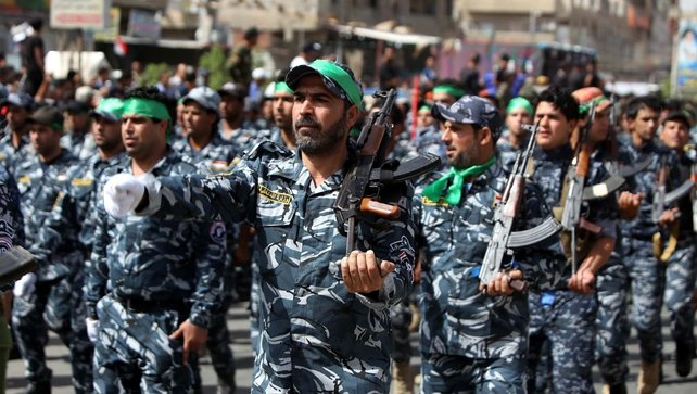 Members of the Shia militia 'Peace Brigades' parade in Baghdad in a show of strength against militants