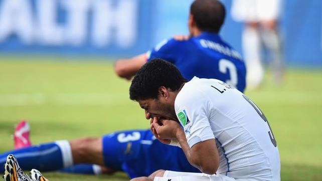 Suarez checks his teeth following his clash with Chiellini