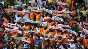 Ivory Coast fans cheer for their team before the start of the game against Greece