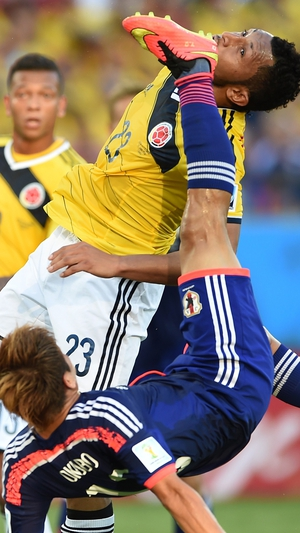 Japan's Yoshito Okubo (bottom) and Colombia's Carlos Valdes contorting in contention for the ball