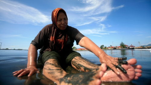 An Acehnese woman cleans her legs with sand on a beach during the holiday before the Muslim fasting month of Ramadan, at Syiah Kuala Beach, Banda Aceh, Indonesia
