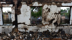 Residents walk past a house wrecked by shelling in the besieged Ukrainian city of Slaviansk