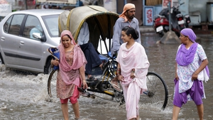 Women walk through a water-logged street after a spell of heavy pre-monsoon rain in Amritsar, India