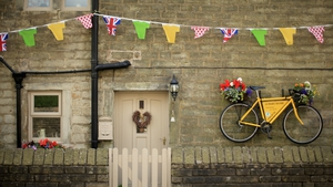 A yellow bicycle hangs outside a stone cottage in Yorkshire, England as the county prepares to host the first stage of the Tour de France