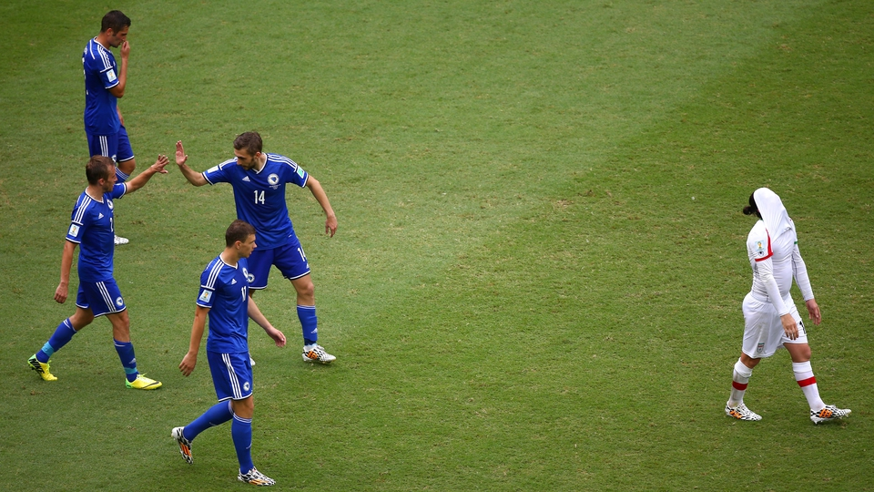 Bosnia-Herzegovina players celebrate their second goal as it's all a bit much for an Iranian player