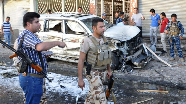 Iraqi security forces walk past a burnt out car at the site of a car bomb explosion in Kirkuk