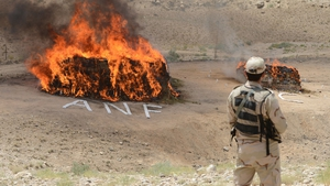A Pakistani soldier stands guard beside a burning pile of seized drugs during a ceremony to mark International Day against Drug Abuse and Illicit Trafficking