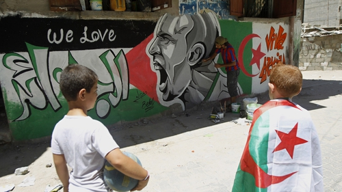 Palestinian boys, one weraing an Algerian flag, looks at graffiti-artist, Belal Khaled painting a portrait Italian football player Andrea Pirlo in Gaza