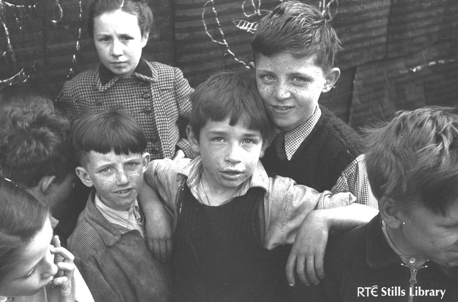 Children stand beside a corrugated iron fence, Dublin